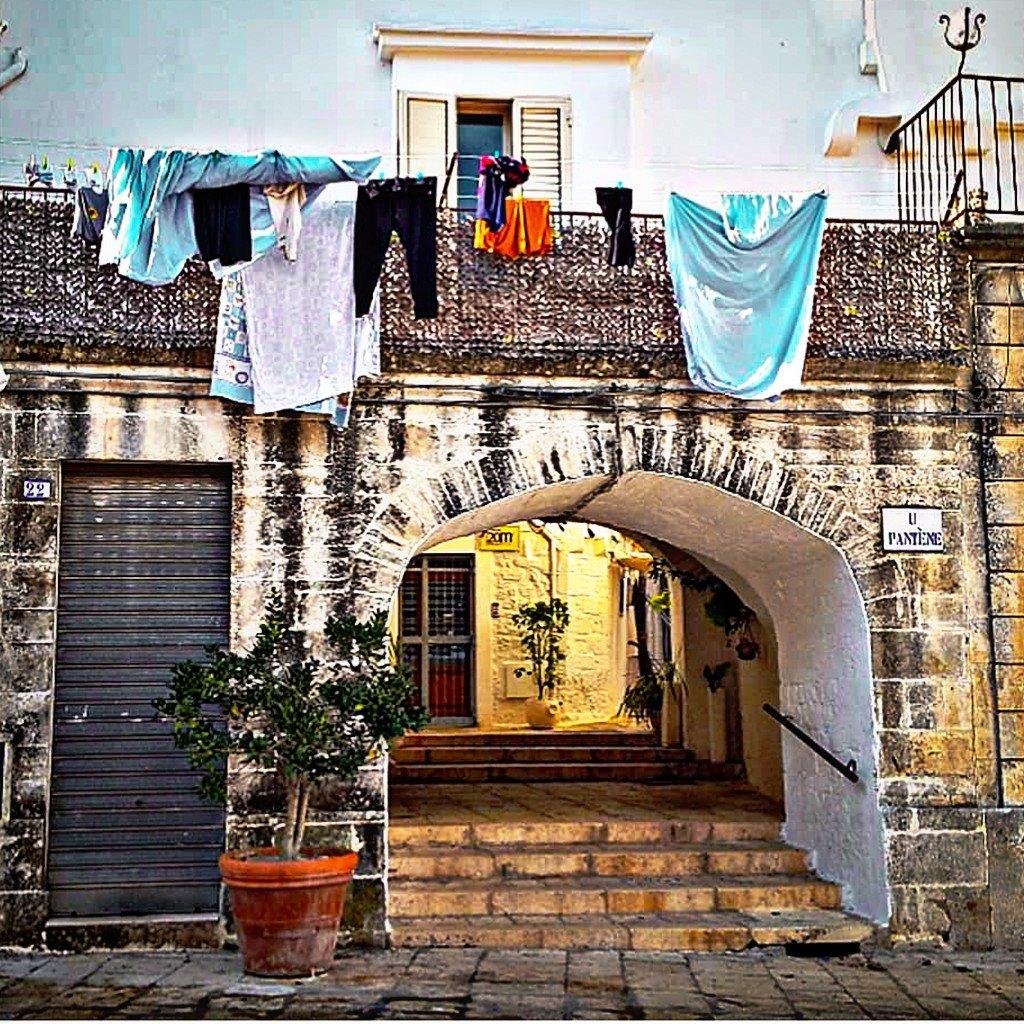 vicolo di Cisternino con arco e antica casa con balconata e panni stesi
