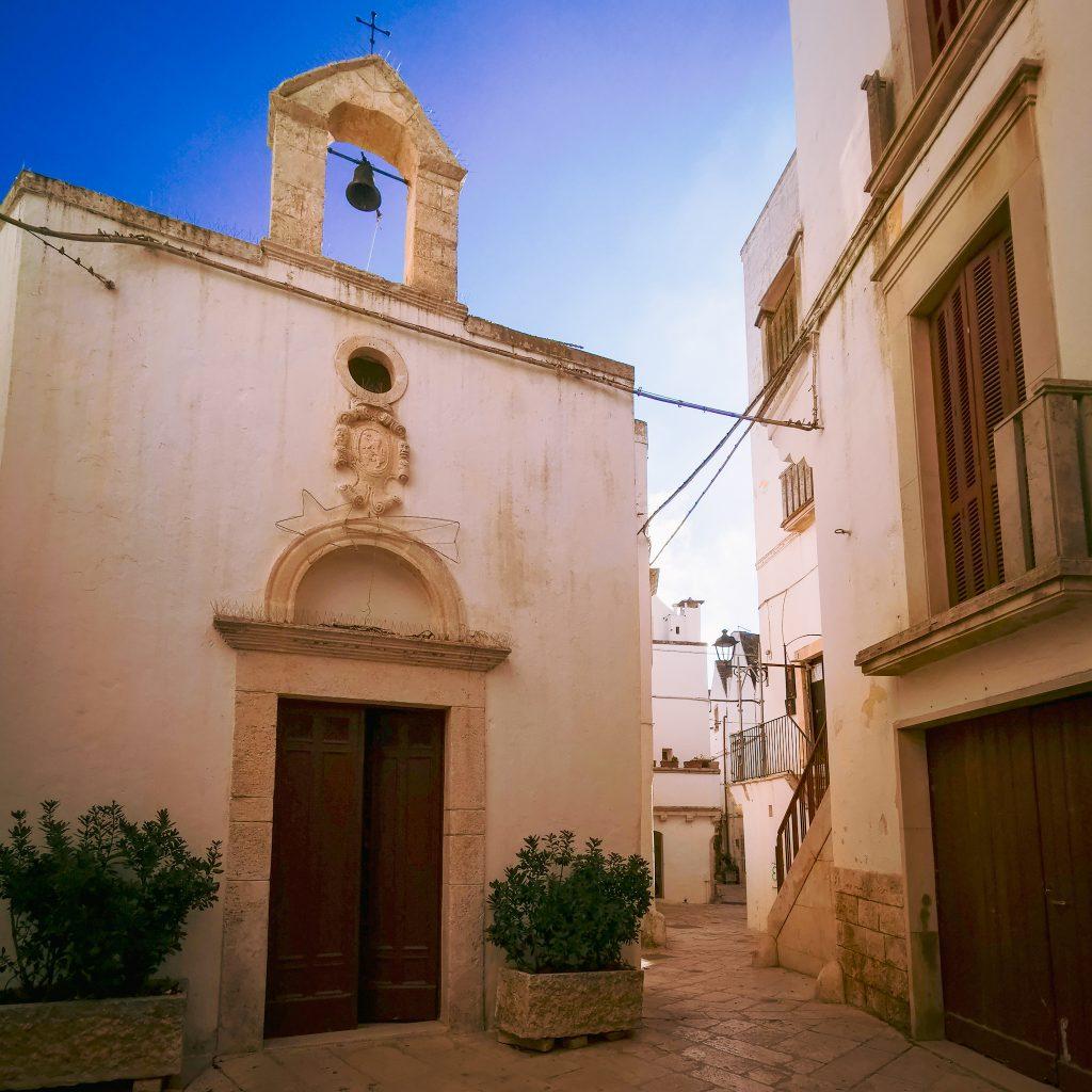 chiesetta nel centro storico di Locorotondo con campanella in cima, case intonacate di bianco con persiane marroni