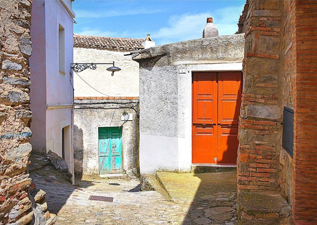6 parchi letterari in Basilicata: vivolo di Tursi con case dalle porte colorate e antico lampione