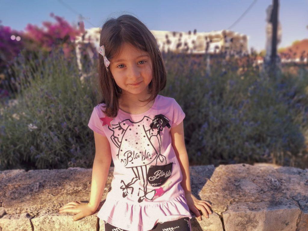 Bambina seduta su muretto a secco con cespuglio di lavanda alle spalle