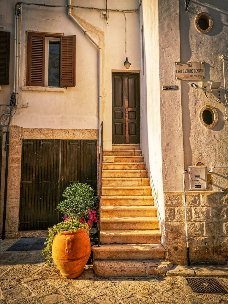 Casa antica con scaletta in muratura, grandi anfore fiorite, una persiana aperta e due oblò