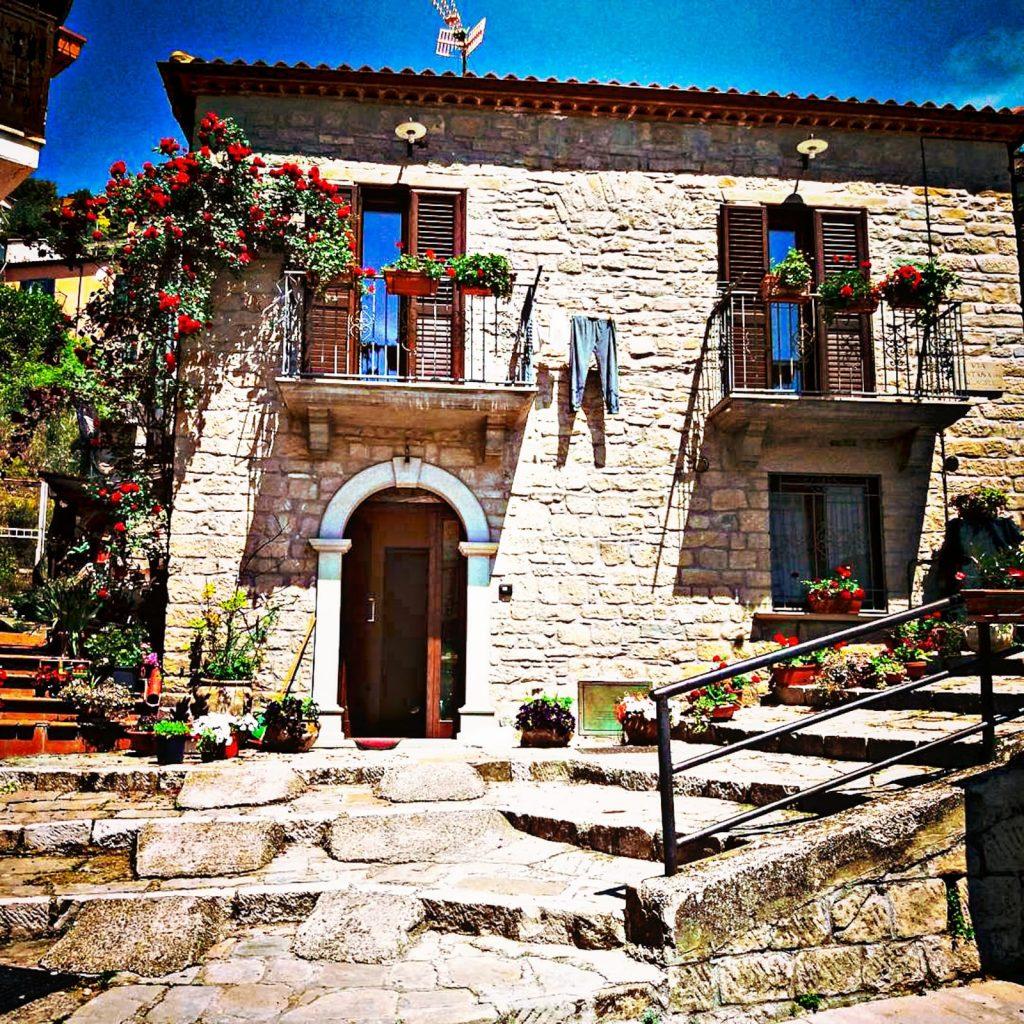 casa graziosa di pietra con moltissimi fiori ai davanzali e scaletta