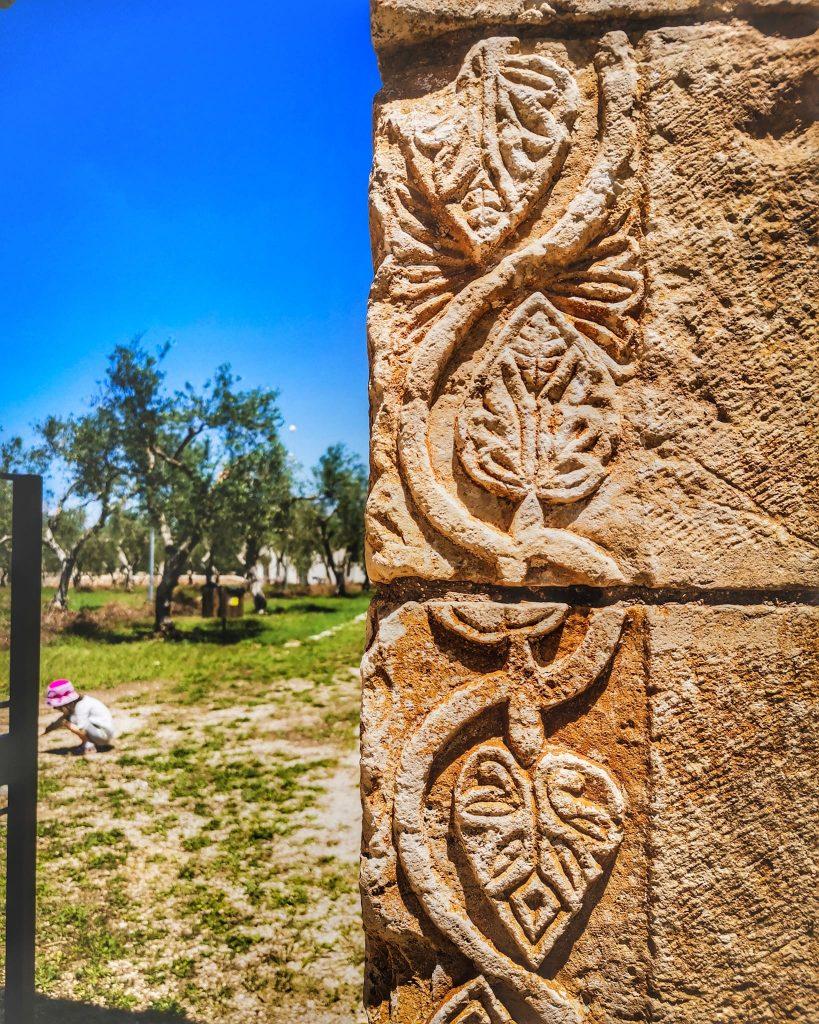 Dettaglio di fregio sul portale del castello di Balsignano. Ulivi e bambina sullo sfondo