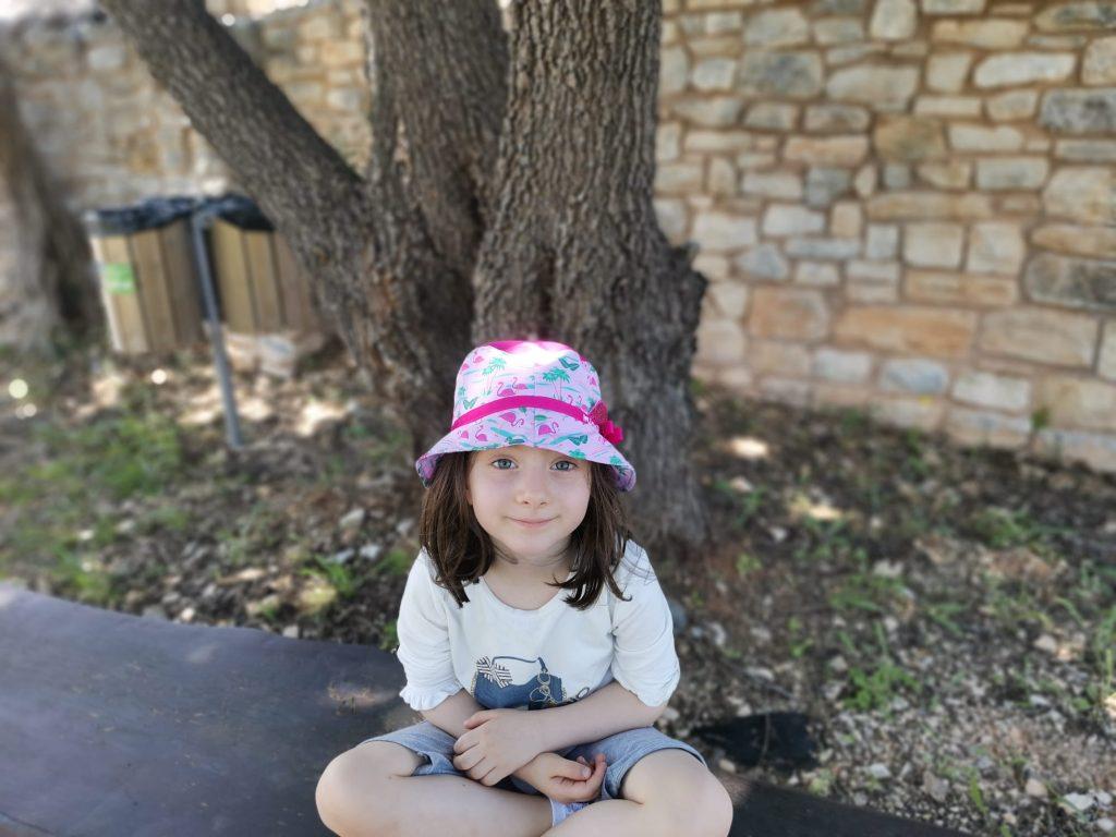 bambina con cappello seduta a gambe incrociate su una anca all'ombra di un grosso albero