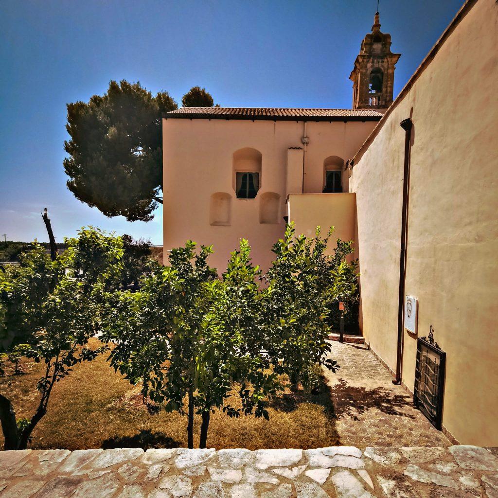 campanile e fianco di un convento, alberi di ulivo, stazioni di via crucis