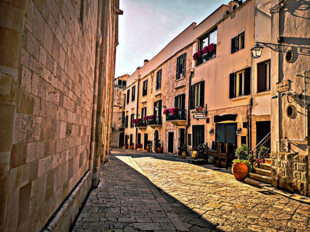 Vecchia strada lastricata con graziose case piene di fiori ai davanzali, un lampione di foggia antica e molte persiane verdi