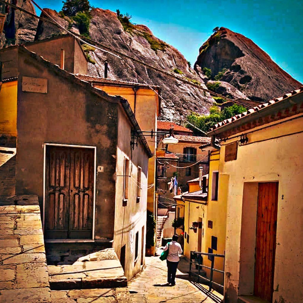 vicolo in discesa fra case gialle con le montagne sullo sfondo e una signora con borsa verde che cammina