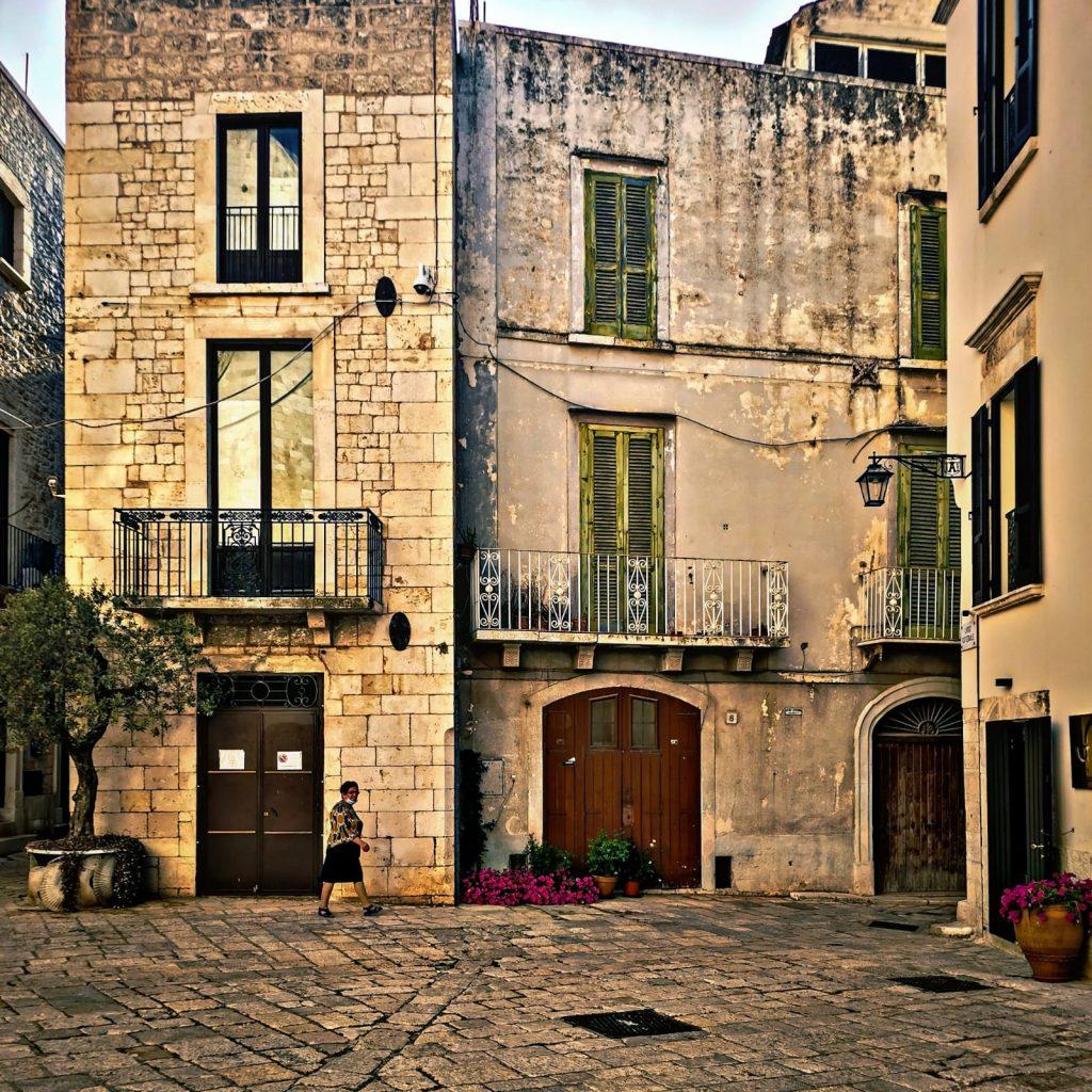 Vicolo con antiche case con persiane verdi e balconcini. Fiori nei vasi agli angoli della strada, un'anziana passante