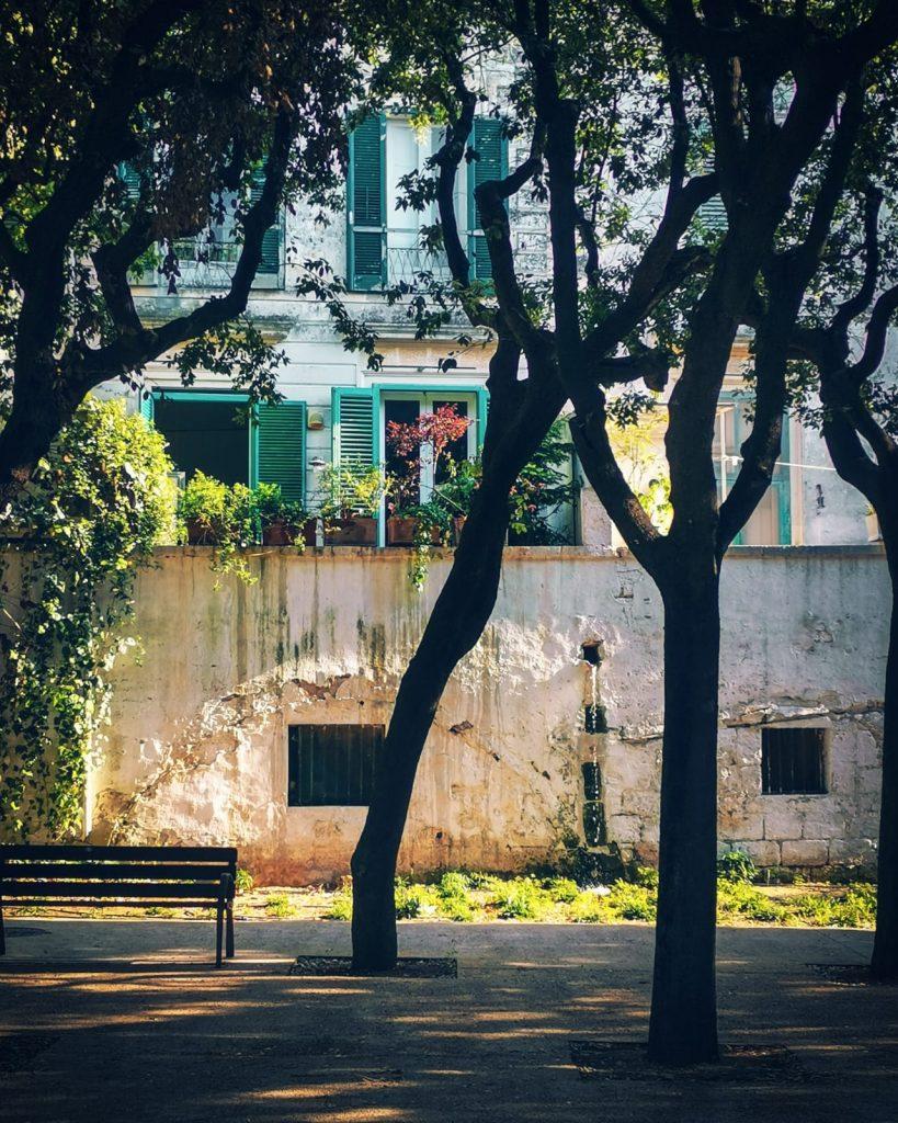 Villa comunale con piccola fontana e panchina vuota, case con persiane verdi sullo sfondo