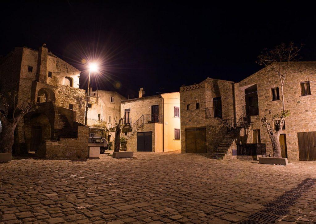 Piazzetta di Aliano nella notte con casette di pietra, scale di accesso, alberi e basolato