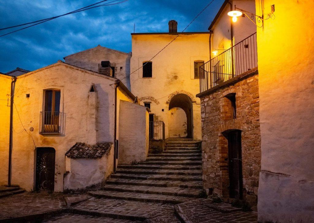 Aliano e i suoi antichi vicoli di notte. Case addossate e scalette. Lampioni accesi