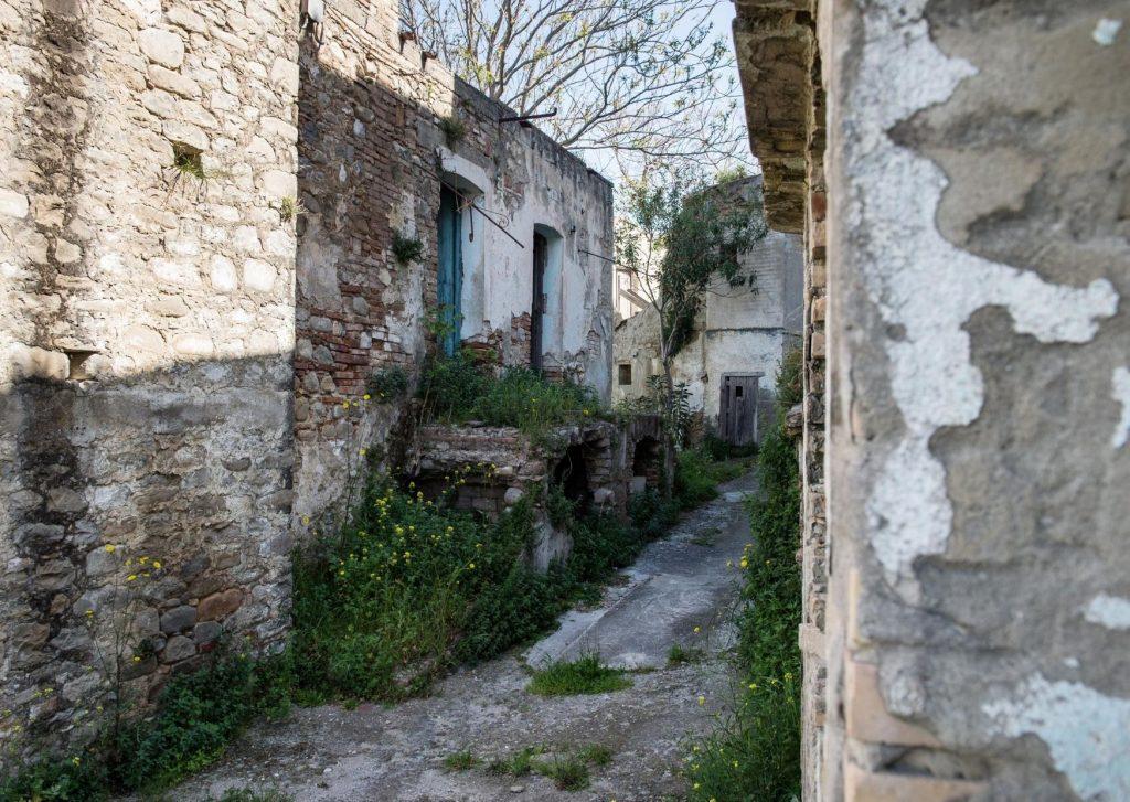 Vicoli abbandonati di Aliano con l'erba che spunta dalle case e dalle pietre