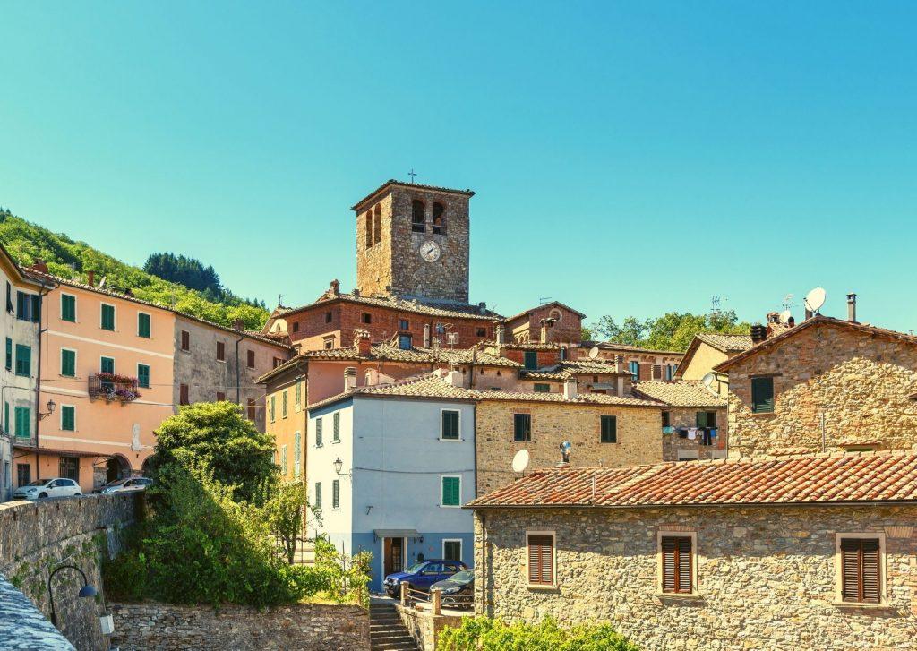 borghi dove andare a vivere: case di pietra con tetti spioventi a Montieri, resti di mura e vegetazione
