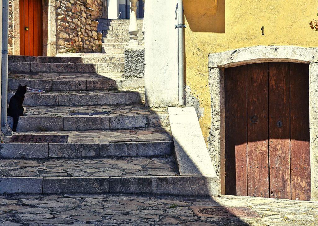 borghi dove andare a vivere: scorcio di zungoli con scale di pietra, porte di legno antico, gatto nero