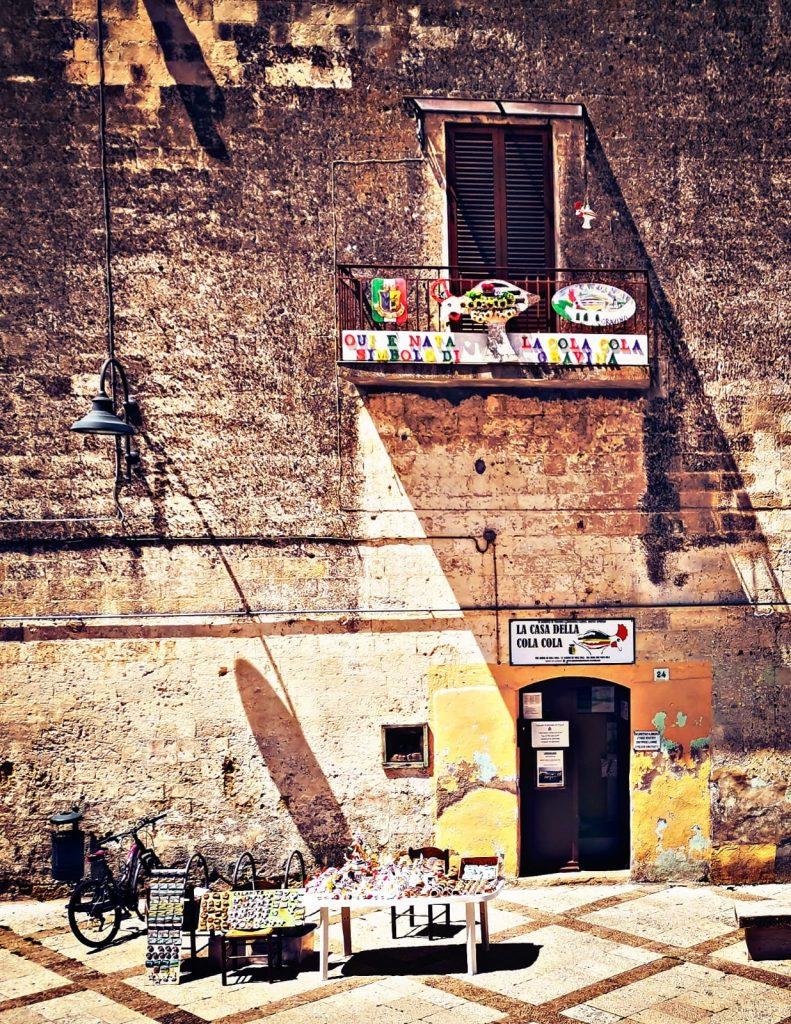 Casa Museo della Cola Cola: ingresso con balcone decorato, banchetto con fischietti di terracotta in vendita