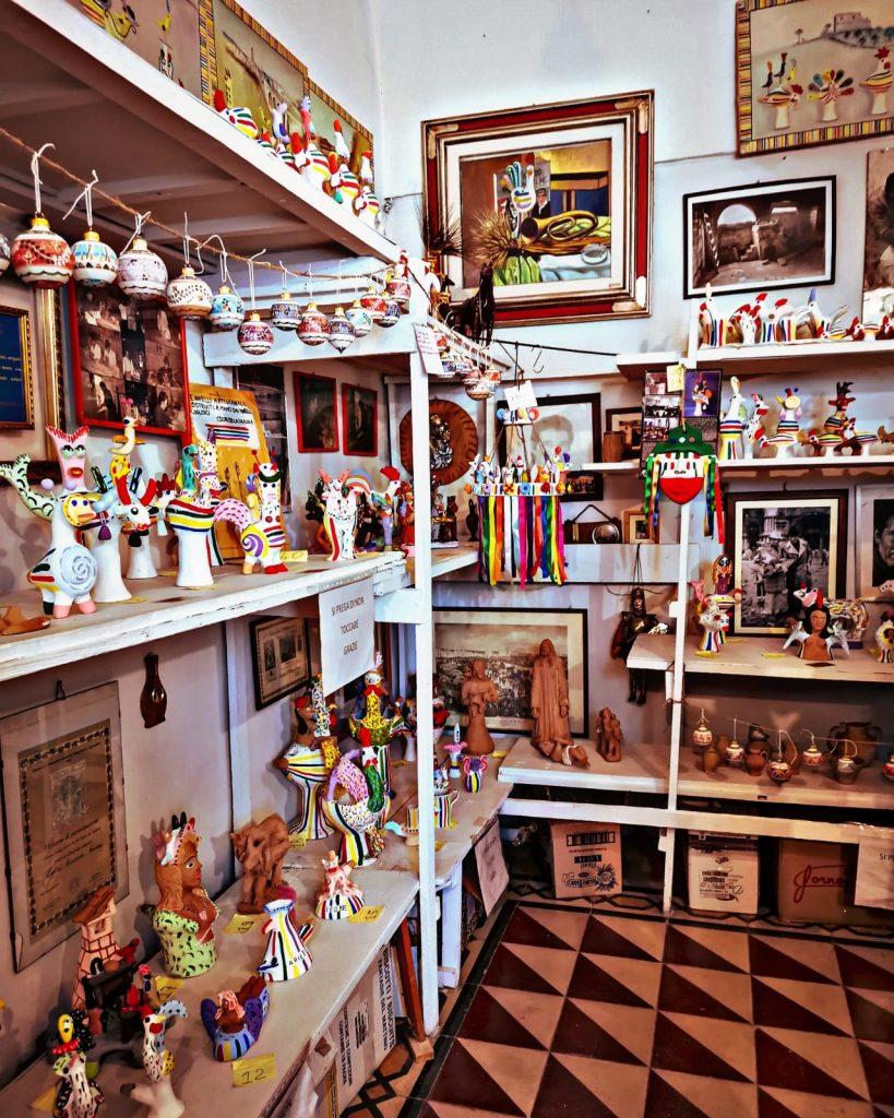Casa Museo della Cola Cola: scaffali pieni di terrecotte colorate, fischietti, animali, decorazioni. Pavimento con decorazioni geometriche