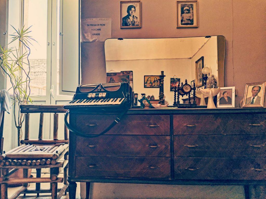 Casa Museo della Cola Cola: specchiera con fotografie, soprammobili, fisarmonica e foto antiche. Finestra