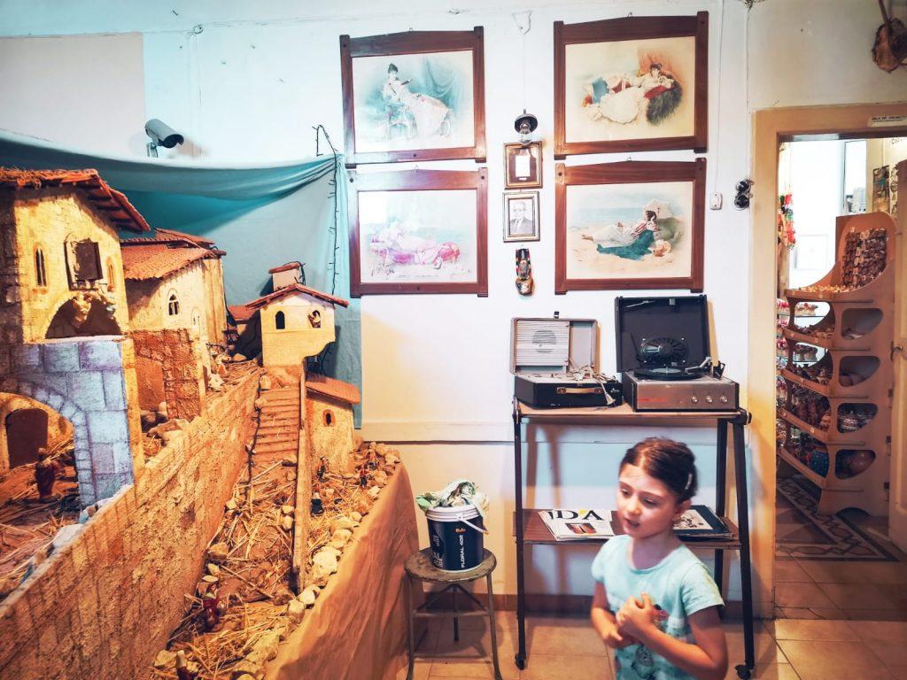Casa Museo della Cola Cola: presepe artigianale, quadri grammofono e scaffali oltre una porta aperta. Bambina che osserva
