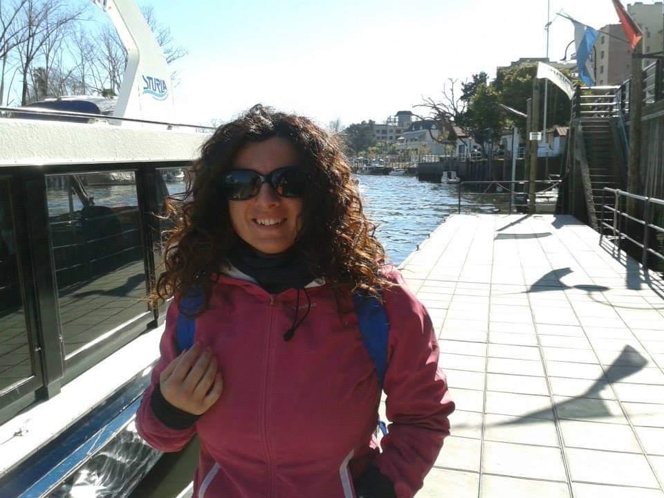 Anna davanti a un battello sul fiume in abbigliamento sportivo, zaino blu e grandi occhiali da sole