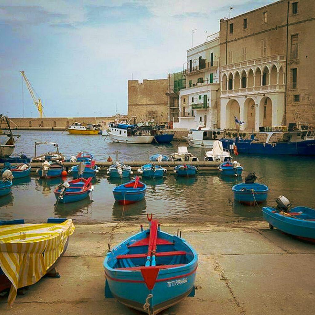Monopoli: Cala Batteria. Porticciolo con i gozzi azzurri e rossi e il palazzo in stile veneziano che si specchia sull'acqua