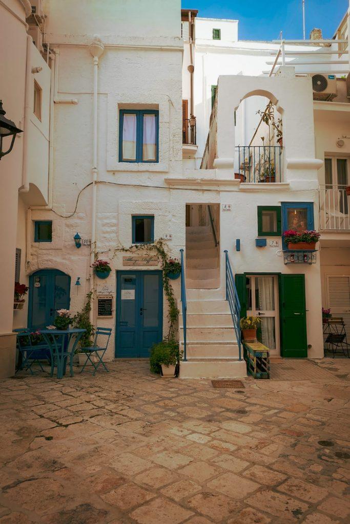Monopoli: chiasso o clasustro con pavimento basolato e case dalle persiane azzurre, balconcini fioriti, terrazzo, piante rampicanti