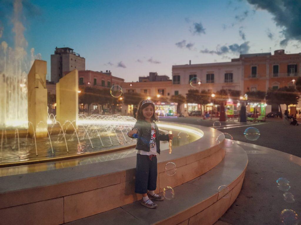 Monopoli: piazza Vittorio Emanuele. Fontana illuminata con bimba che gioca con le bolle di sapone. Giostrine e lecci in lontananza