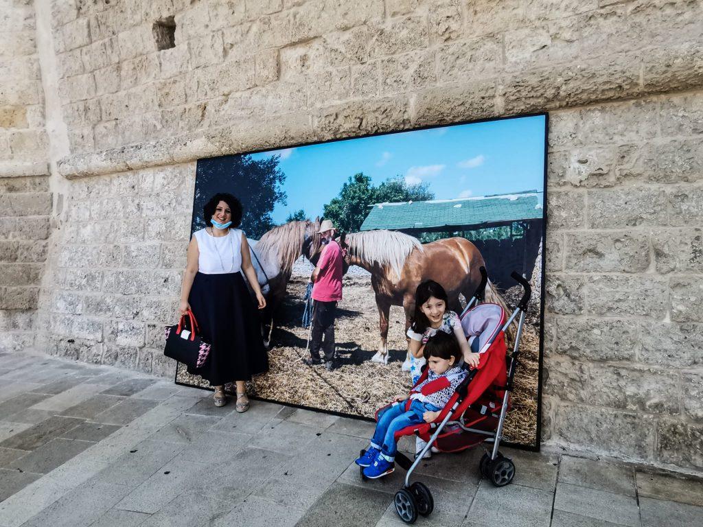 PhEst 2020: foto sulle mura del porto e famiglia che posa davanti alla foto