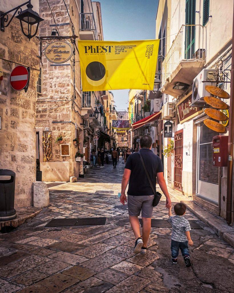 PhEst 2020: via Garibaldi con lo stendardo giallo del festival. Papà e bambino che camminano mano nella mano