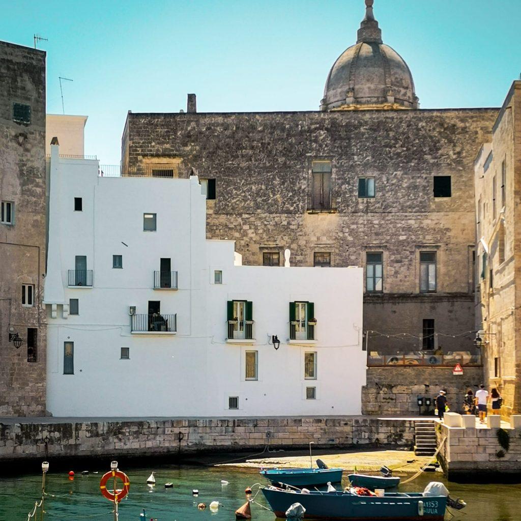 Monopoli: case bianche affacciate sullo specchio limpido del mare. Una cupola barocca che emerge oltre il profilo dei vecchi palazzi, barche in primo piano