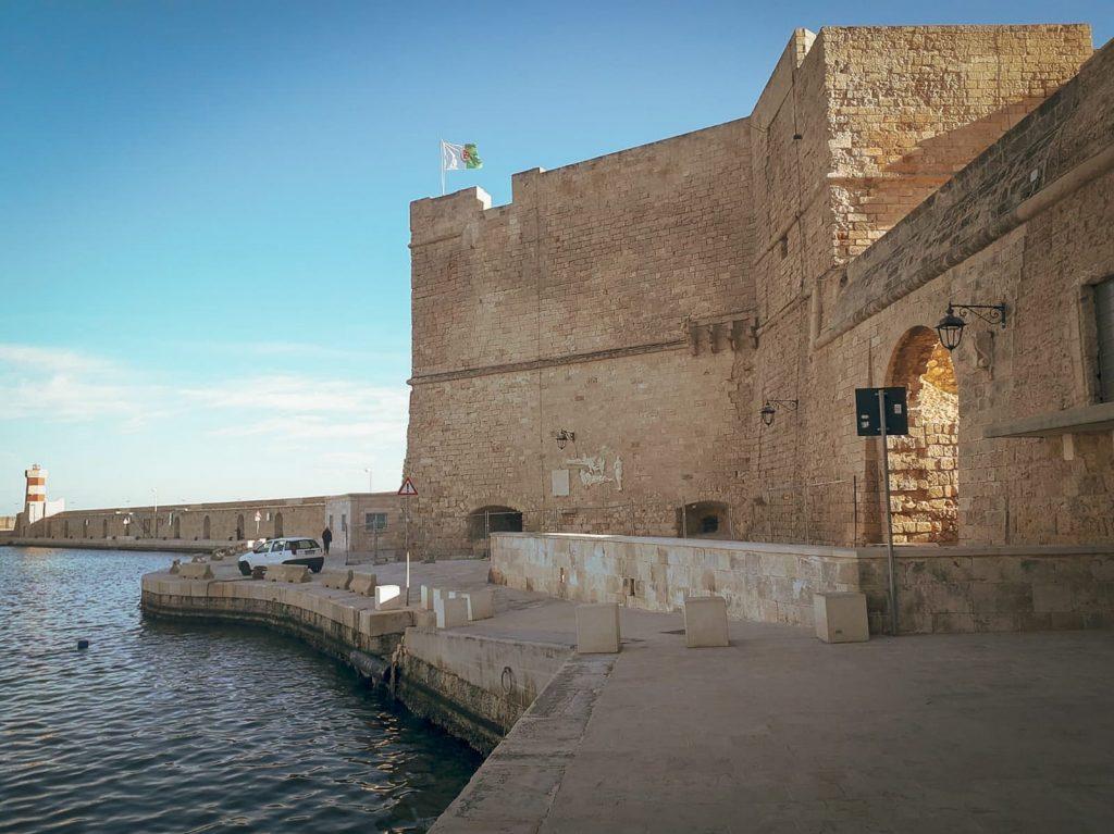 Monopoli, castello di Carlo V affacciato sul mare, in lontnananza il faro di tramontana con le sue strisce bianche e rosse