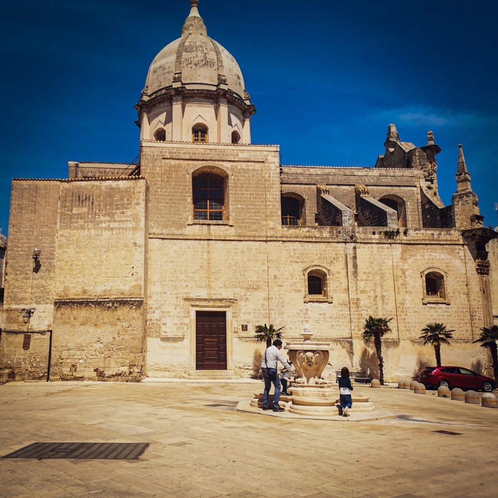 Monopoli: piazza Palmieri con fontana e chiesa barocca sullo sfondo nella luce del mezzogiorno