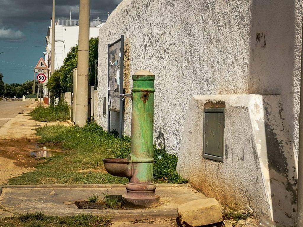 Fontana verde davanti a un muro bianco su strada di campagna.