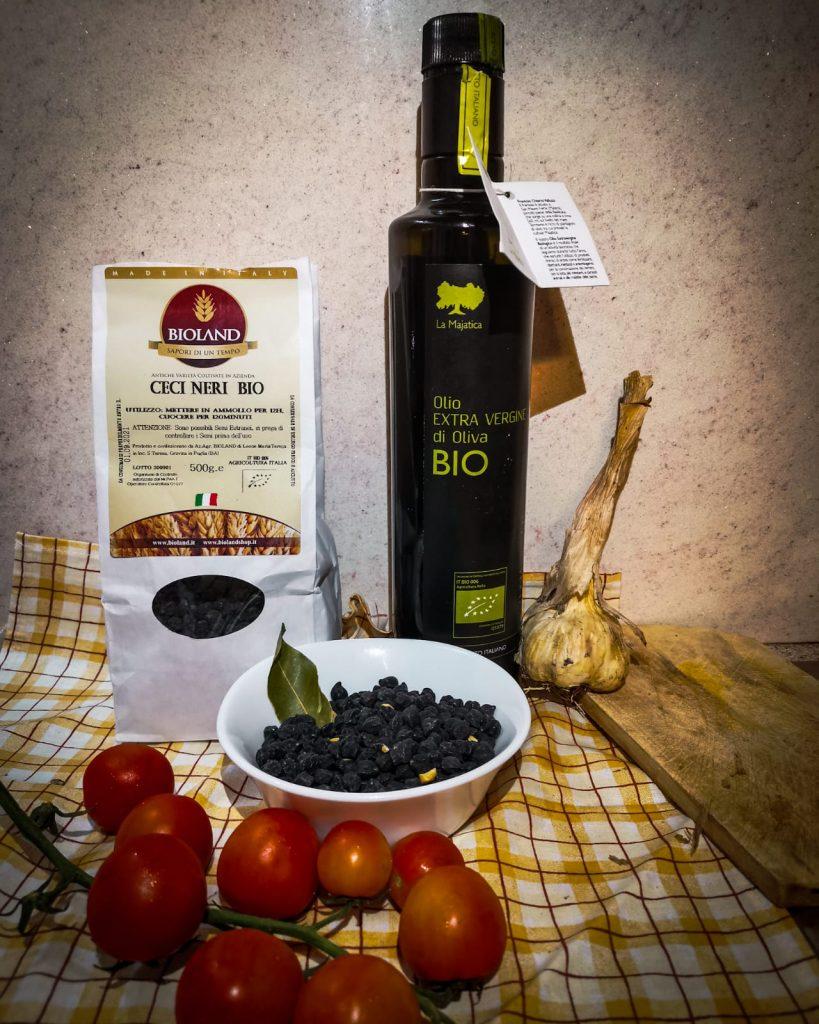 ceci neri della Murgia in ciotola e in confezione con pomodorini, alloro, testa d'aglio, olio biologico