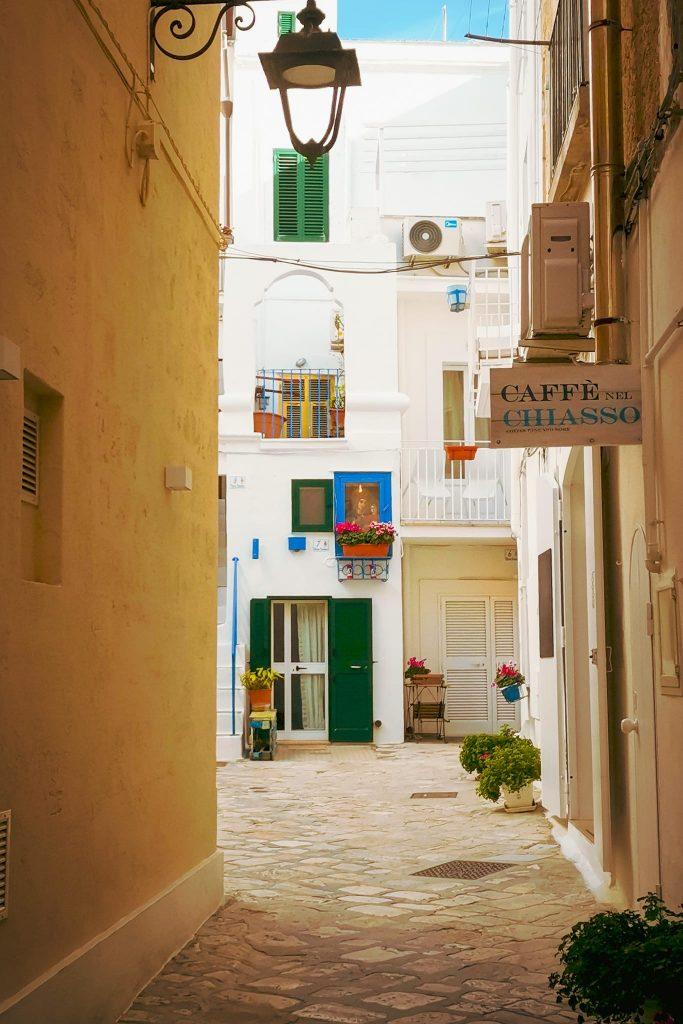ingresso nel chiasso con lampione antico, insegna del caffè, porticine colorate, finestre con persiane, madonnina nella teca