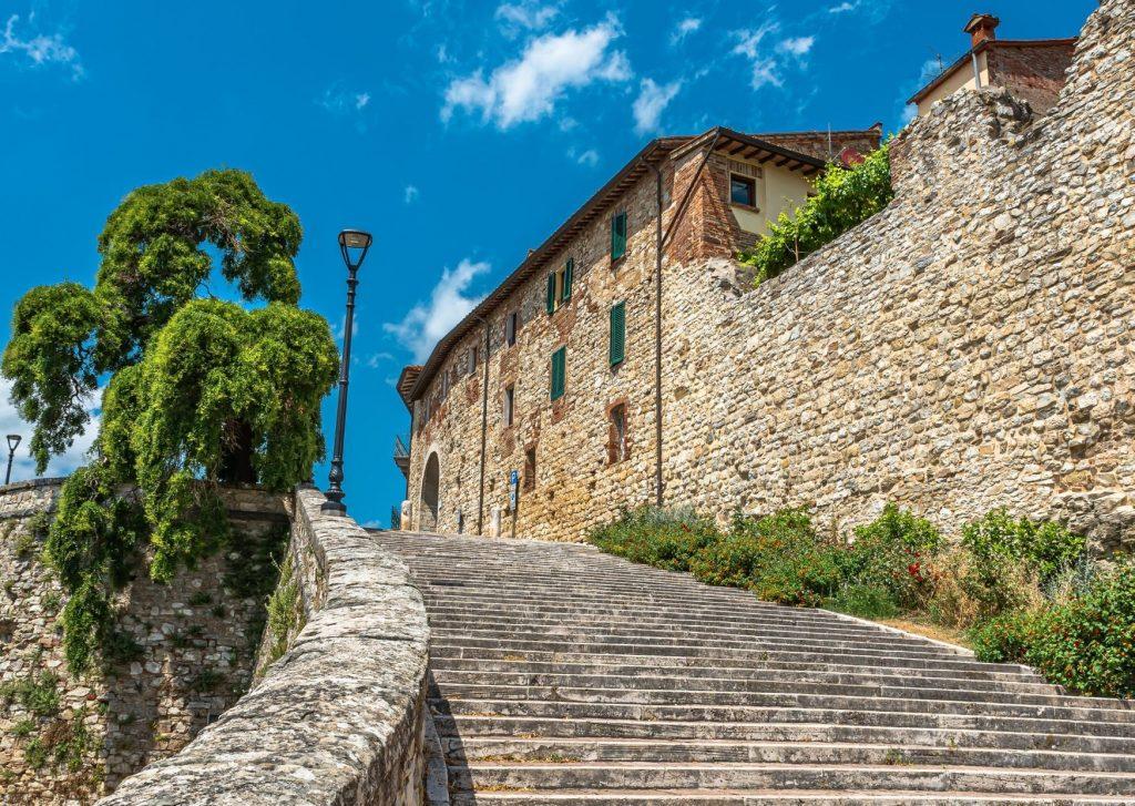 Scalinata di pietra che corre lungo antiche abitazioni tutte in pietra
