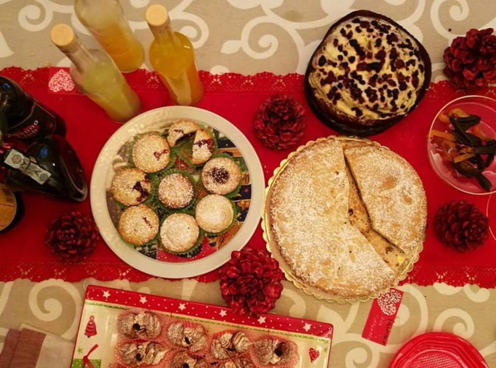 tavola imbandita con dolci natalizi: bocconotti, panettone farcito, torta, paste alla crema
