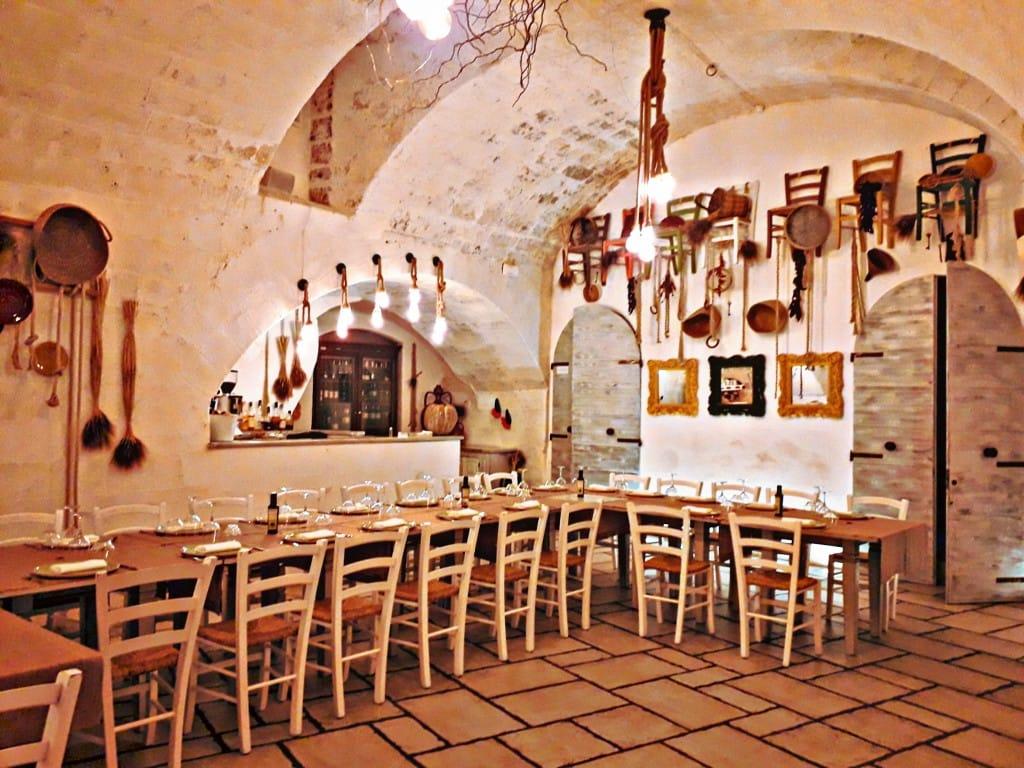 sala dell'osteria radici con tavolata, pareti bianche e antichi utensili appesi