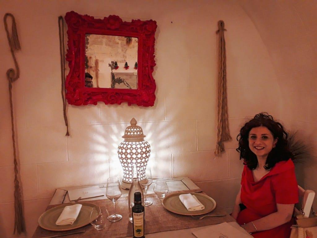 tavolo apparecchiato per due con donna seduta e specchiera rossa shabby chic