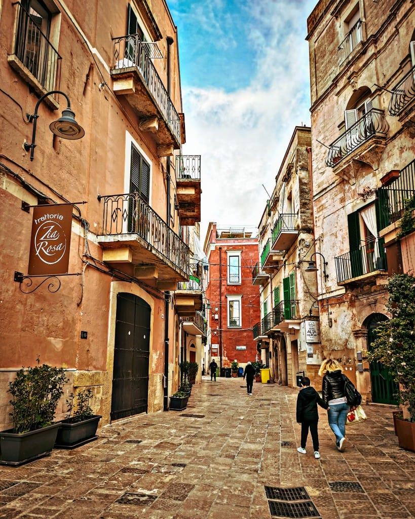 5 ristoranti di Gravina in Puglia: antica strada con insegna del ristorante zia rosa e alcuni passanti