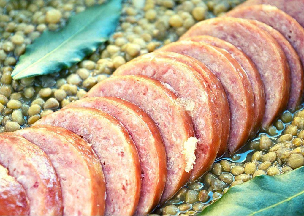 Cotechino su letto di lenticchie con foglie di alloro