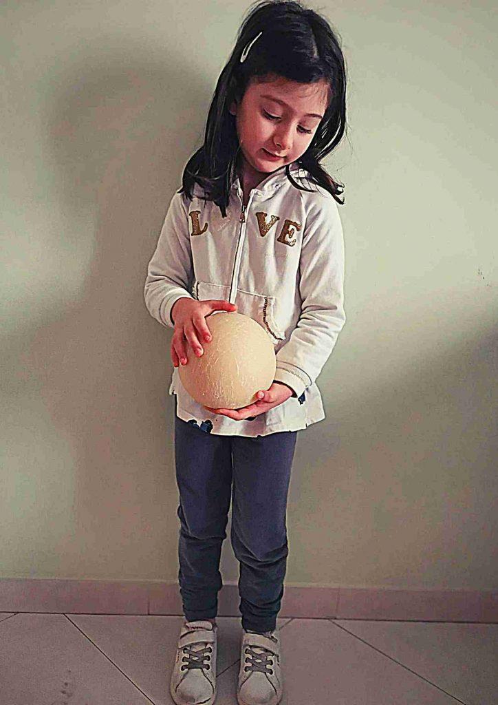 Bambina con forma di formaggio fra le mani