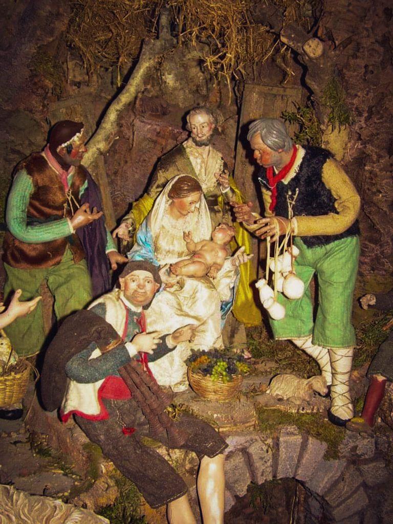 Dettagli di un presepe napoletano: Vergine, Bambino, San Giuseppe, venditore di formaggi, venditore di uva e altri