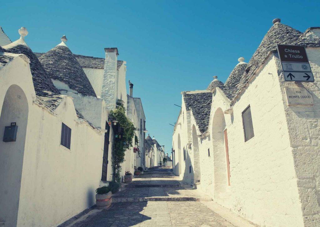 Alberobello: stradina assolata costeggiata da trulli