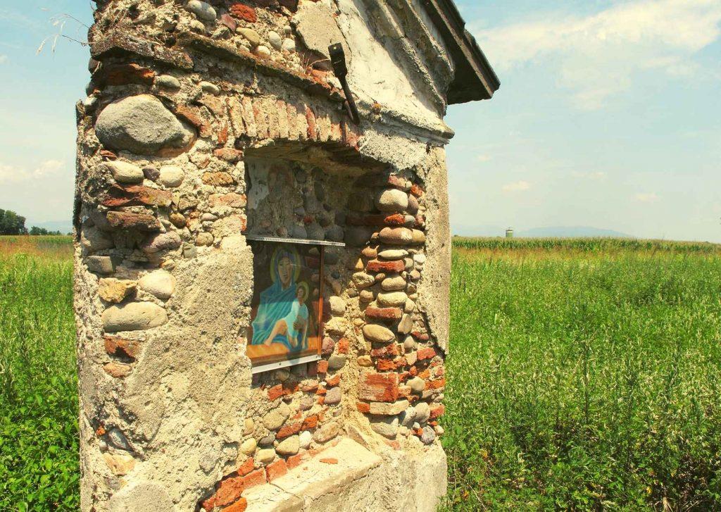 Una santella con Madonna e bambino davanti a un campo di grano
