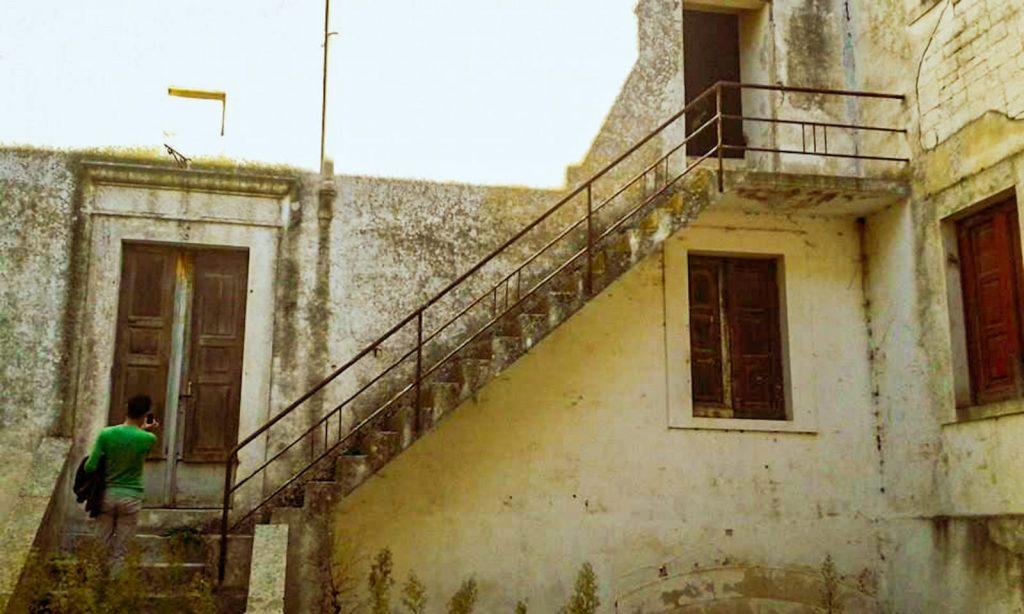 Atrio interno della Casa Rossa con vecchie finestre, porte arrugginite, scale pericolanti