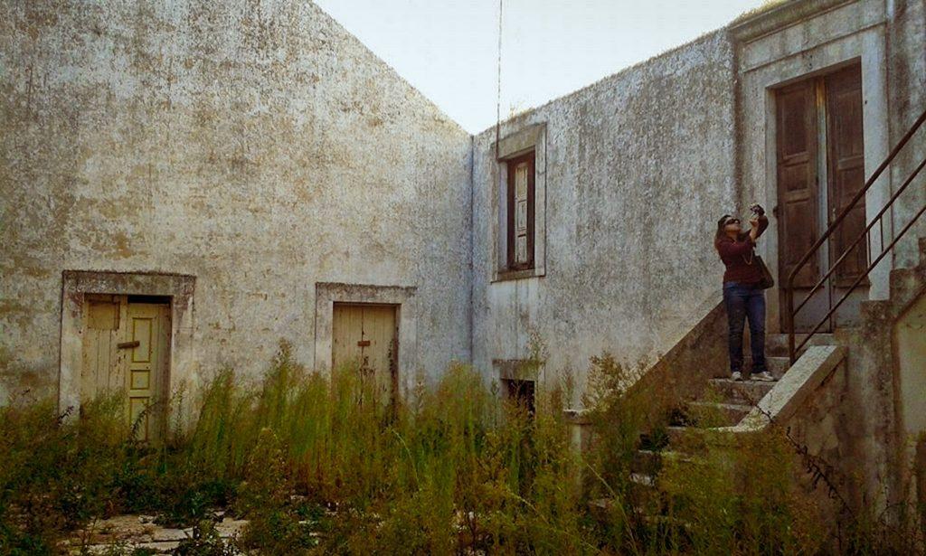 Atrio interno infestato dalle erbacce. Porte chiuse e vecchie finestre in cattivo stato che vi si affacciano