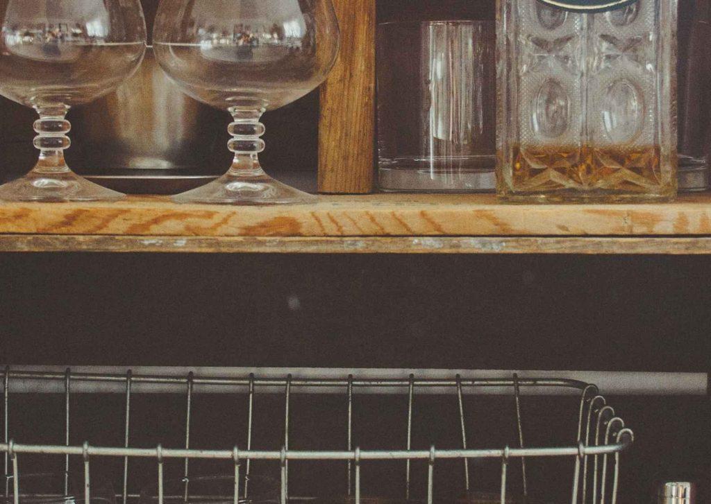 Bicchieri vuoti sul bancone di un bar e bottiglia di whiskey