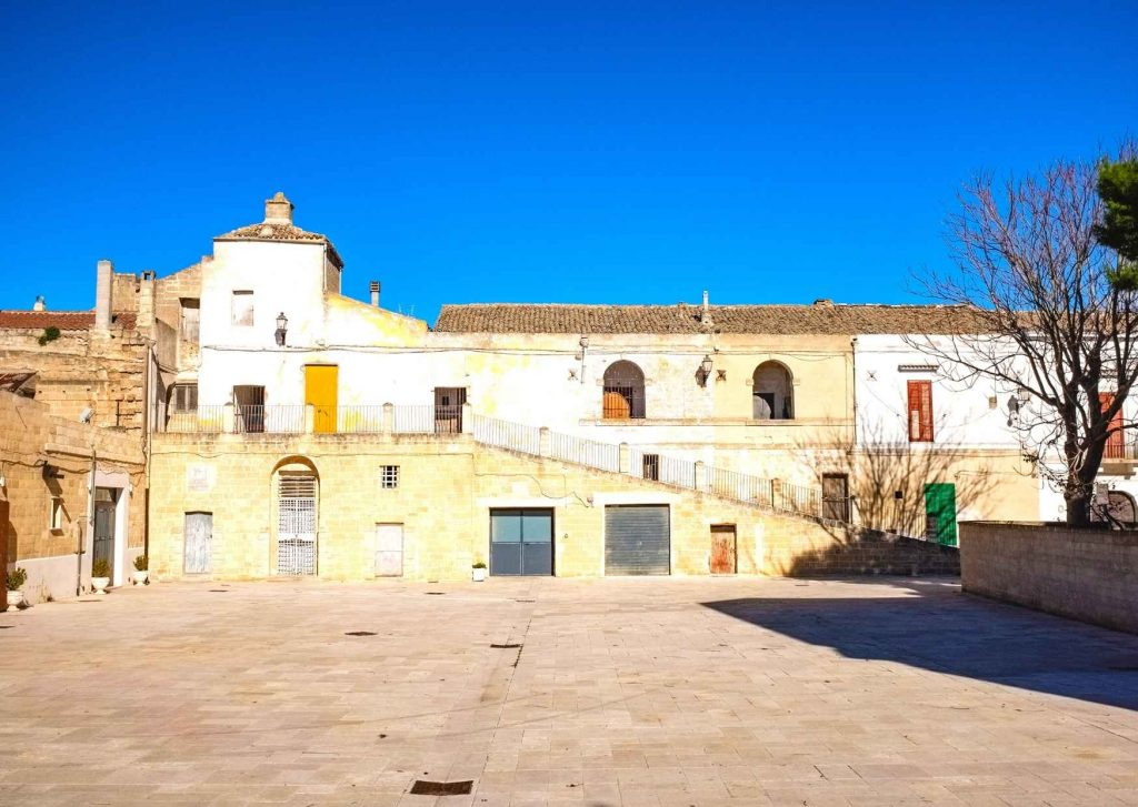 antico palazzo in giallo con scalinata. Piazzale antistante ristorante e birreria