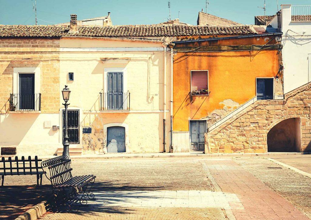 Panchina, lampione e antiche case gialle