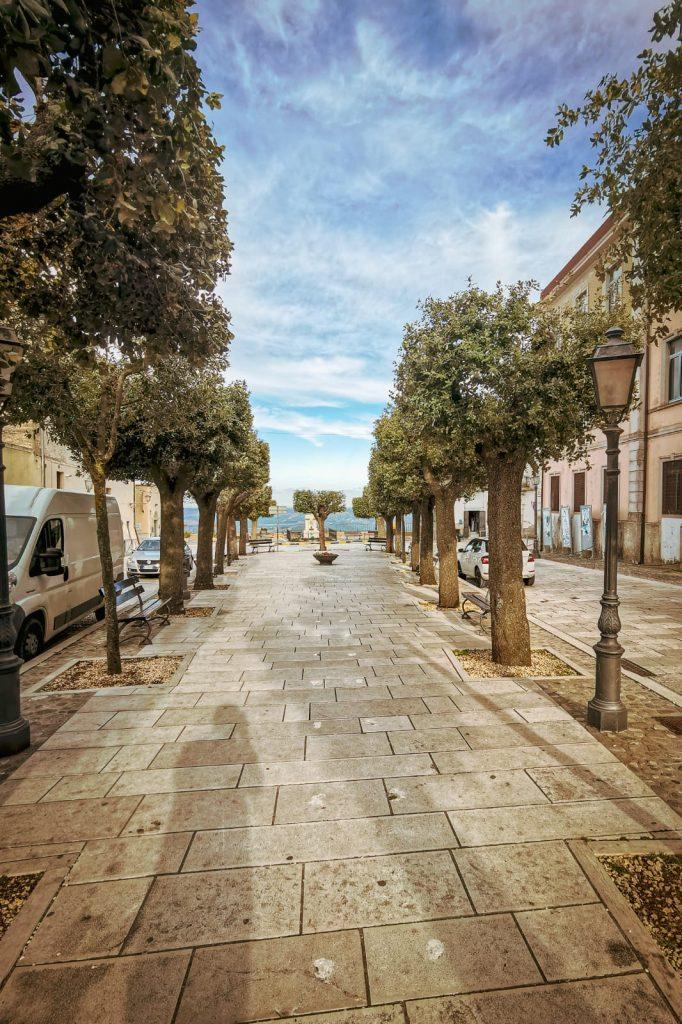 Irsina: piazza Garibaldi con alberi e lampioni, il belvedere in fondo ed eleganti palazzi ai lati